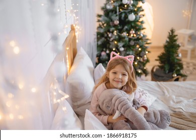 girl with cat ears sits on the bed against the background of the New Year tree. Hugs a toy elephant and smiles at the camera