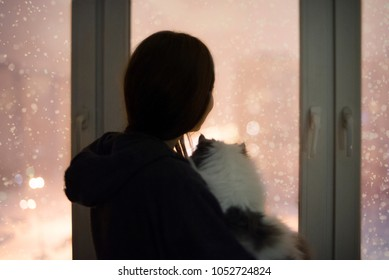 girl and cat looking out the window at the snow