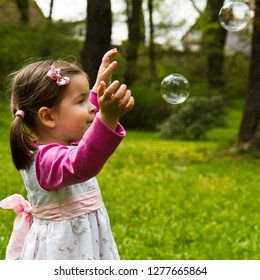 girl catches soap bubbles in the park