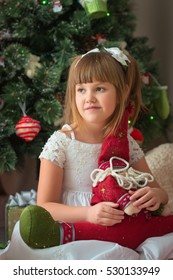 Girl cautiously looks away from the camera, holding a doll in the hands against the background of the Christmas tree in traditional colors