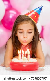 Girl celebrating his birthday and blowing candles on cake