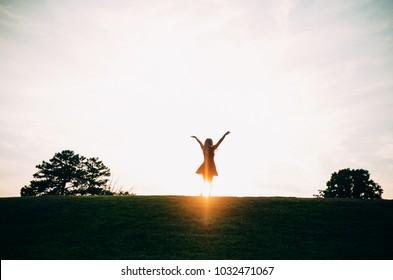 Girl Celebrating in the Sunset