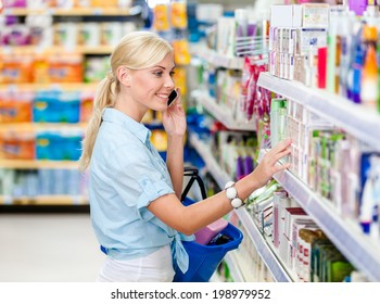 Girl with cellphone at the shop choosing cosmetics among the great variety of products. Concept of consumerism, retail and purchase