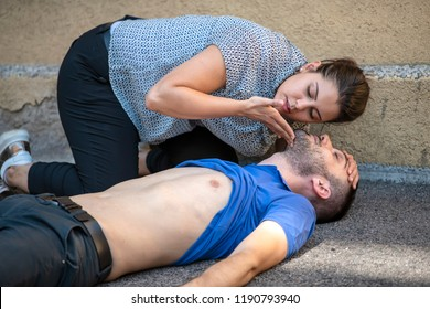 girl checking the breathing of an unconscious guy after heart attack