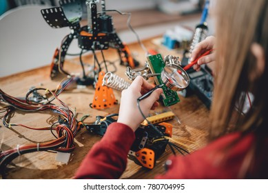 Girl checking circuit board with multimeter on the wooden table at home and building a robot as a school science project