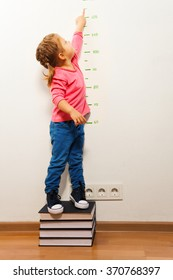 Girl checking height on growth chart at four books