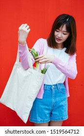 A girl checking the leek in her canvas bag infront of the red wall.