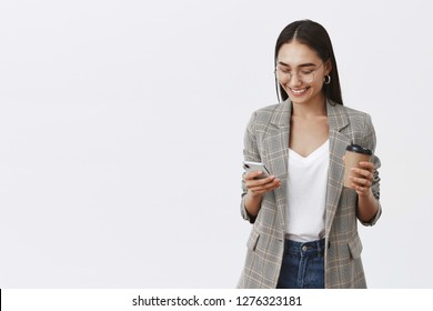 Girl checking messages, talking with friends, making new appointment. Portrait of confident busy female entrepreneur in glasses and jacket, holding cup of coffee and smartphone, using gadget