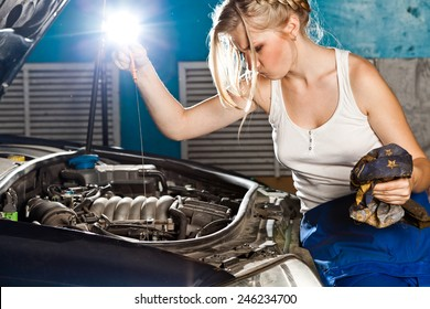 Girl checks the oil level with dipstick in their own broken car
