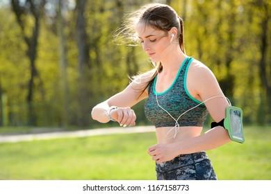 Girl checks pulse on fitness bracelet or activity tracker pedometer on wrist