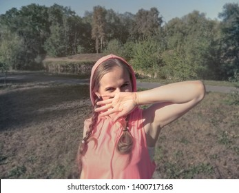 A girl with cheerful, playful, mischievous eyes covers her face with her hand. A cute young woman in pink clothes in the park, photo using filters and effects, in soft light pastel colors