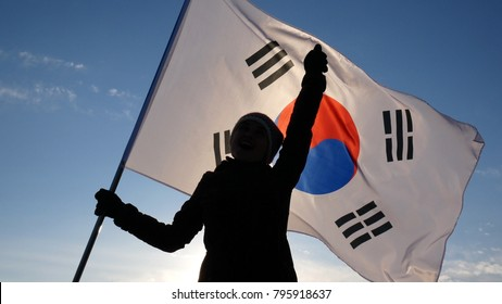 Girl cheerleader with South Korean flag rejoices and supports athletes.