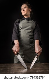Girl chef with knives on a dark background. Studio photography