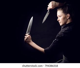 Girl chef looks at knife, dark background, studio