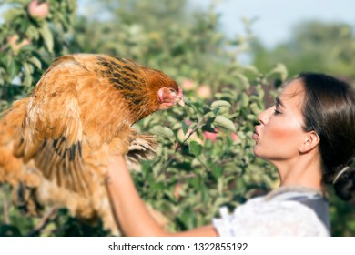 girl with chicken in hand in the garden