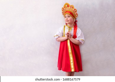 Girl, child 5 children in Russian dress, sundress and kokoshnik. In the hands of a wicker basket. On a light background, copy space