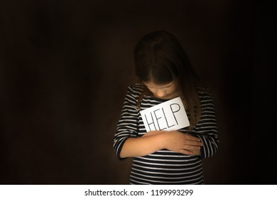 Girl child ask for help, concept children's problems and deprivation, on dark background