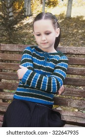 Girl child in autumn on the street in a striped sweater