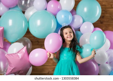 Girl child with balloons in the studio