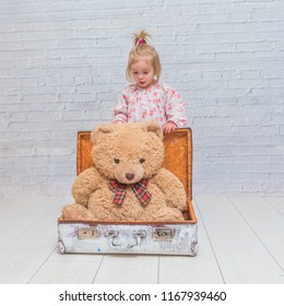 girl, child with bear and suitcase on white brick wall background