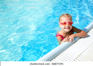 girl child in blue water of the swimming pool