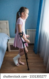 Girl child with a broken leg in a cast is standing on crutches and looks out the window