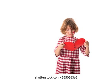 Girl child in checkered dress connects paper broken red heart on a white background