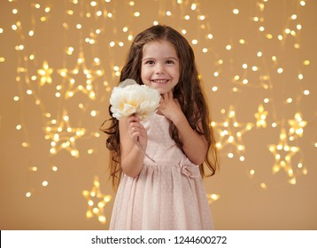 girl child is in christmas lights, yellow background, pink dress