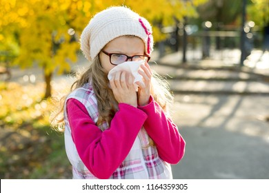 Girl child with cold rhinitis on autumn background, flu season, allergy runny nose.