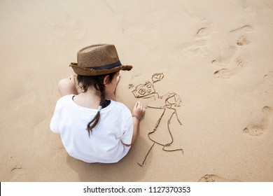 The girl the child draws in the sand
