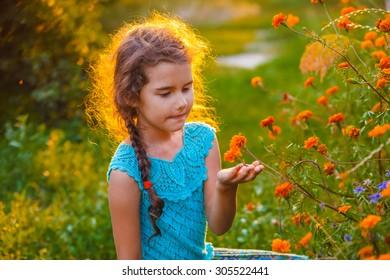 Girl child explores exploring orange flower in nature sunset summer photo outdoor areas
