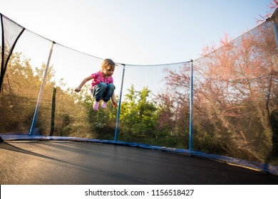 Girl child jumping on trampoline in backyard