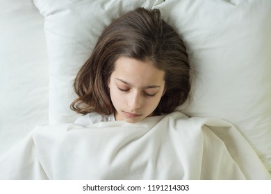 Girl child with long brown hair sleeping on a pillow in bed.