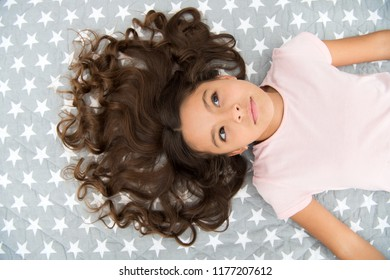 Girl child with long curly hair lay on bed top view. Child perfect curly hairstyle looks cute. Conditioner mask organic oil keep hair shiny and healthy. Amazing curls tips. Make it curly but natural.