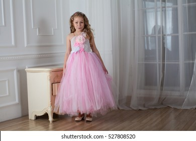 Girl child with long hair stand on white and open arms, dressed in pink. The child in a pink dress