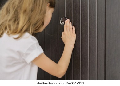 Girl child looking in the peephole at the front door.