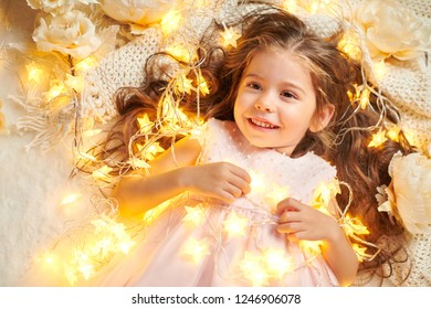 girl child is lying with christmas lights and flowers, face closeup
