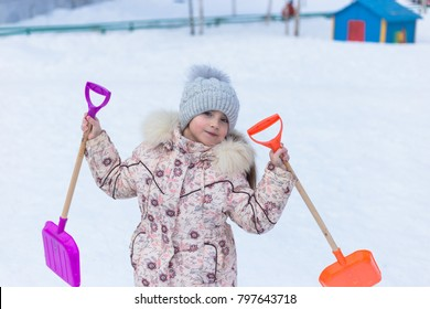 Girl child on a walk winter shovel happiness