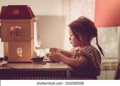 Girl child with a pigtail plays with a dollhouse on a table in the dark with a lamp, a fabulous photo