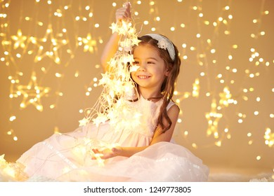 girl child is playing with christmas lights, yellow background, pink dress