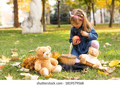 girl child playing on strava with bears in autumn park - Shutterstock ID 1819579568