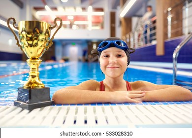 Girl child in the pool with the champion trophy , sunglasses, ha
