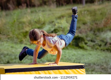 Girl Child Practicing Parkour Gymnastics Outside on Vaulting Horse