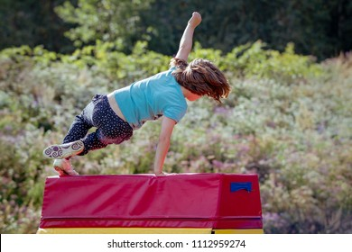 Girl Child Practicing Parkour Gymnastics Outside on Vaulting Horse