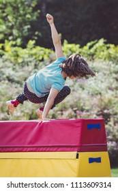 Girl Child Practicing Parkour Gymnastics Outside on Vaulting Hor