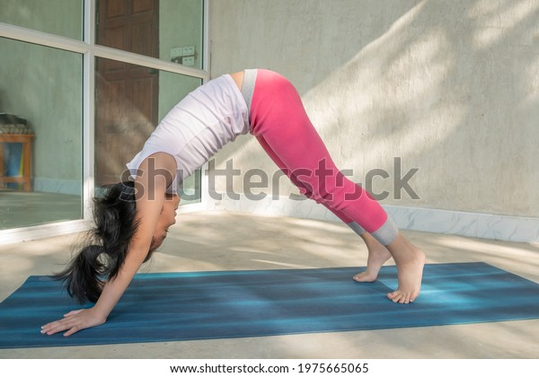 Girl child practicing yoga, standing in downward facing dog exercise, adho mukha svanasana pose, working out wearing sportswear, singlet, pants, indoor full length, white loft studio background.