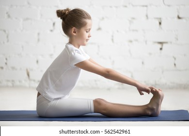 Girl child practicing yoga, stretching in paschimottanasana exercise, seated forward bend pose, working out, wearing sportswear, indoor full length, white loft studio background