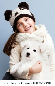 girl child in a scarf and hat hugs a puppy in the studio