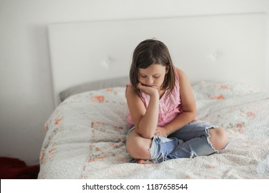 Girl child serious and frustrated sitting on a bed in a bright bedroom, concept age crisis and childhood insults