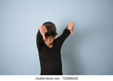 Girl child showing a thumb down gesture